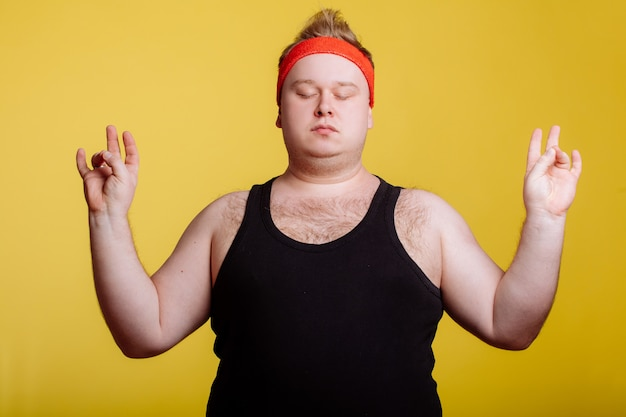 Uomo grasso che si rilassa con la meditazione sulla parete gialla