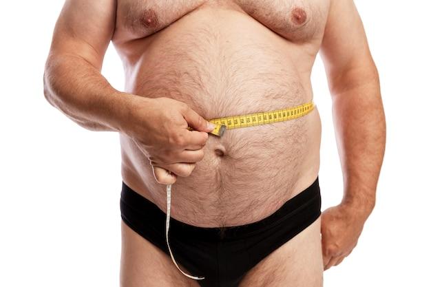 Un uomo grasso in pantaloncini misura il volume dell'addome. isolato. avvicinamento.