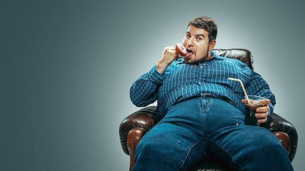 Uomo grasso seduto su una poltrona marrone, emozionato guardando la tv