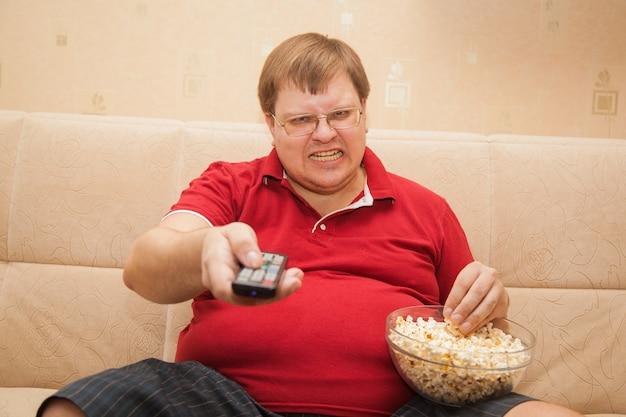 Uomo grasso che guarda tv che mangia popcorn