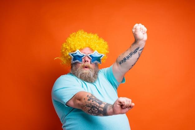 Uomo grasso con barba tatuaggi e occhiali da sole balla musica in discoteca