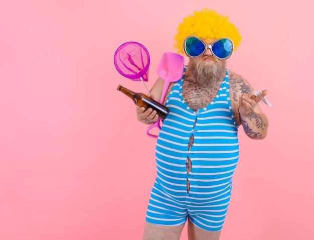 Uomo grasso con barba e parrucca fuma sigarette e beve birra