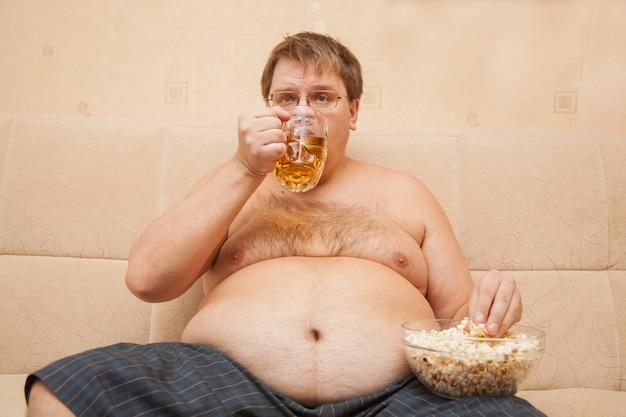 L'uomo grasso con la pancia di birra davanti alla tv mangia popcorn e beve birra