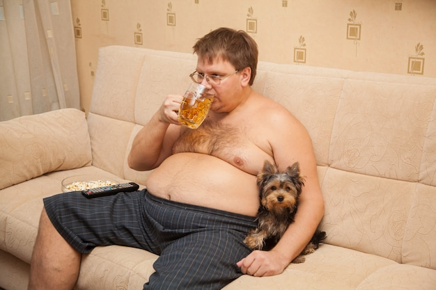L'uomo grasso con la pancia di birra davanti alla tv mangia popcorn con il suo animale domestico