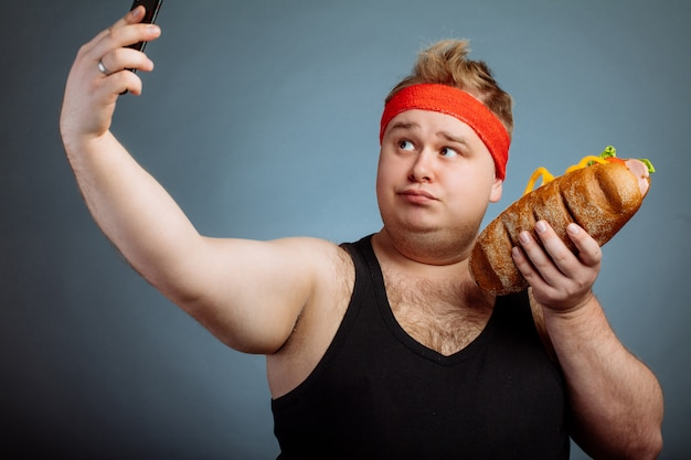 Uomo grasso con sandwich in mano rende selfie