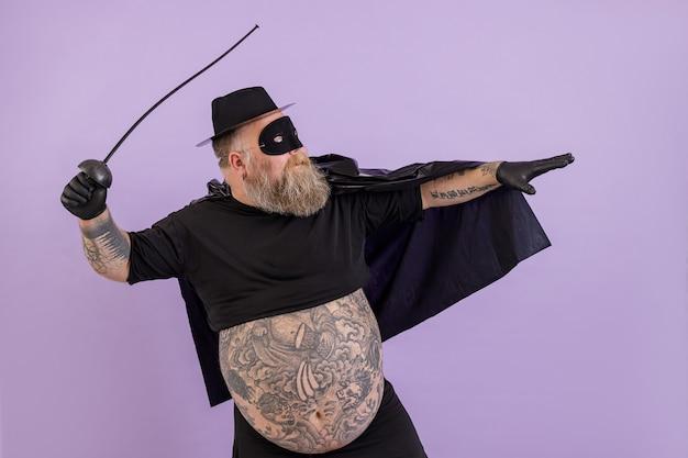 L'uomo grasso in costume da zorro con l'addome nudo sta in posa bellicosa su sfondo viola