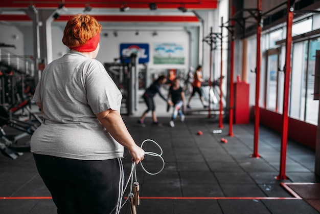 Donna grassa sudata, allenamento in forma con la corda in palestra. calorie che bruciano, persona di sesso femminile obesa su un allenamento in un club sportivo, obesità