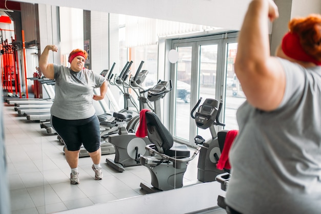 Donna grassa sudata formazione contro lo specchio in palestra. calorie che bruciano, persona di sesso femminile obesa nel club sportivo