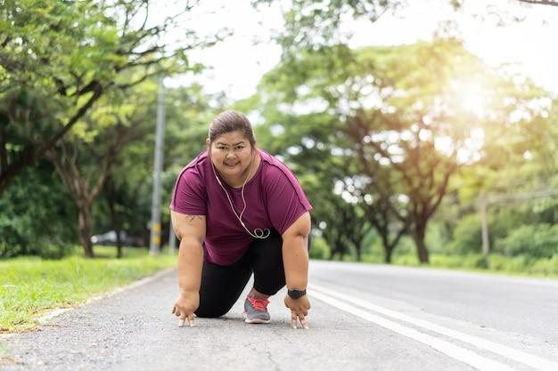 Donna grassa asiatica pronta a correre, si esercita per il concetto di idea di perdita di peso.