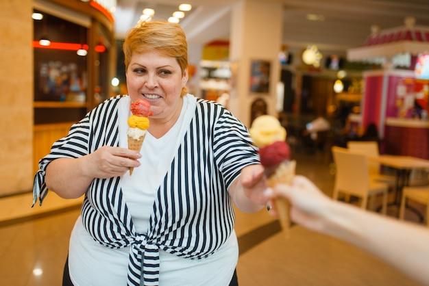 Donna grassa che compra gelati, ristorante fastfood