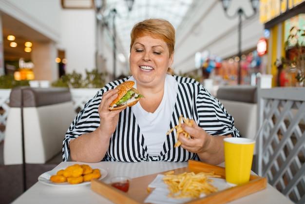Donna grassa che mangia cibo ad alto contenuto calorico nel ristorante fastfood. persona di sesso femminile in sovrappeso al tavolo con cena spazzatura, problema di obesità