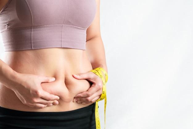 Donna grassa, pancia grassa, mano paffuta e obesa della donna che tiene grasso in eccesso della pancia con nastro adesivo di misura, concetto di stile di vita di dieta della donna