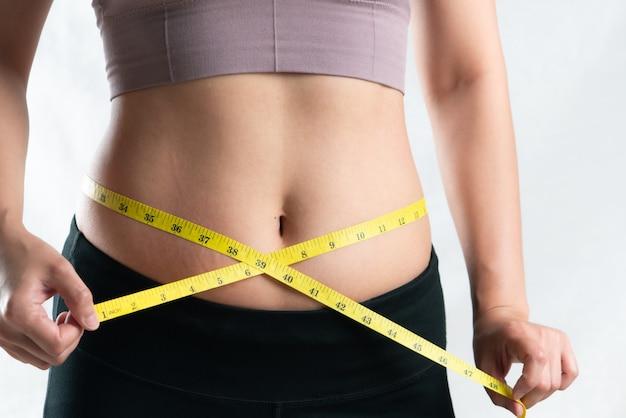 Donna grassa, nastro di misura della holding della mano sulla pancia