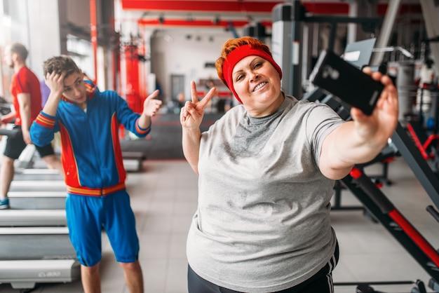 Donna grassa fa selfie con istruttore in palestra, umorismo. calorie che bruciano, persona di sesso femminile obesa nel club sportivo, brucia grassi