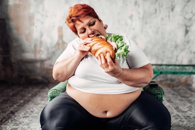 La donna grassa si siede sulla sedia e mangia il panino, bulimico