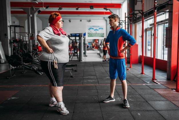 La donna grassa parla con l'istruttore dopo l'esercizio con la corda in palestra.