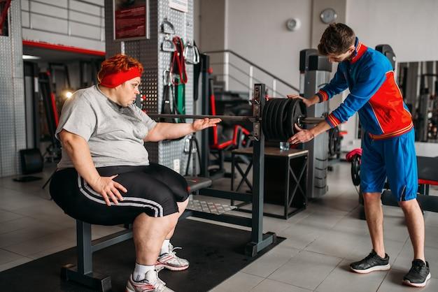 Donna grassa utilizzando bilanciere, formazione con istruttore, duro allenamento in palestra. calorie che bruciano, persona di sesso femminile obesa nel club sportivo, brucia grassi