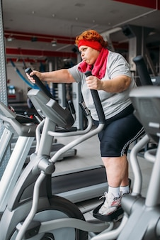 Donna grassa che utilizza macchina ginnica per camminare, allenamento in palestra. calorie che bruciano, persona di sesso femminile obesa nel club sportivo, persone grasse
