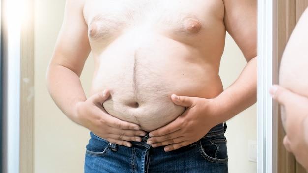 Giovane grasso che sta al grande specchio e che tiene la sua grande pancia grassa. concetto di sovrappeso maschile, perdita di peso e dieta.