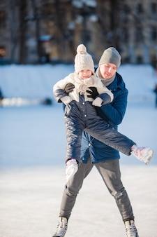 Padre e bambina adorabile divertendosi sulla pista di pattinaggio all'aperto