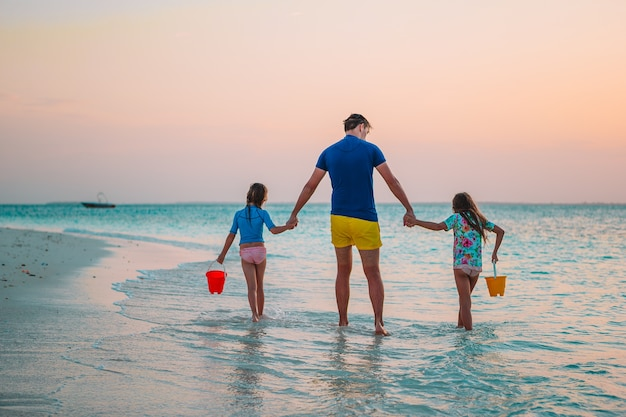 Padre e adorabili bambini piccoli sulla spiaggia tropicale divertendosi