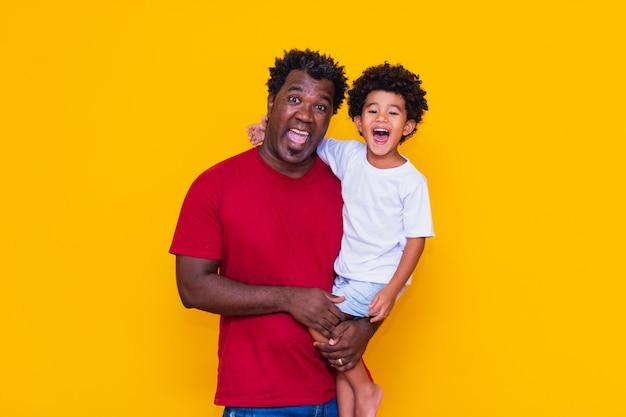 Padre e figlio afro su sfondo giallo sorridente. concetto di festa del papà