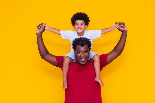 Padre e figlio afro su sfondo giallo sorridendo e giocando. concetto di festa del papà