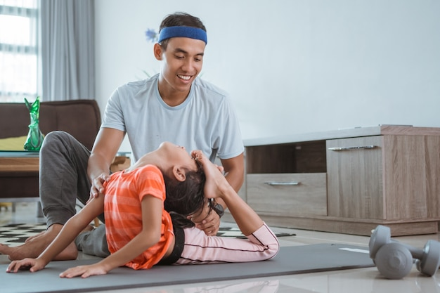 Padre che aiuta sua figlia a fare stretching a casa. bambino che si esercita con il genitore che fa ginnastica