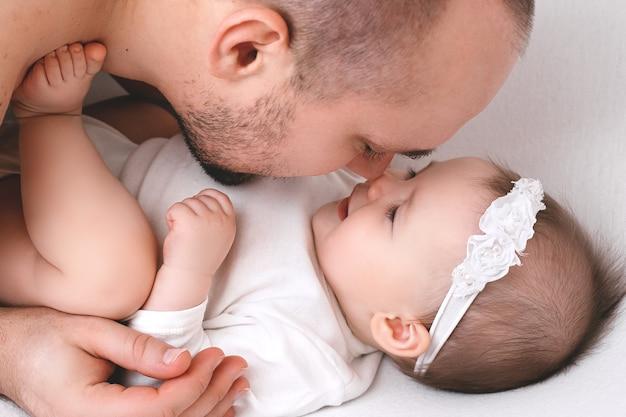 Padre e bambino giocano su un letto bianco in una soleggiata camera da letto