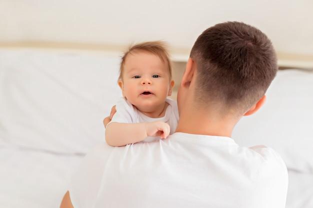 Padre e figlio stanno giocando sul letto bianco nella camera da letto