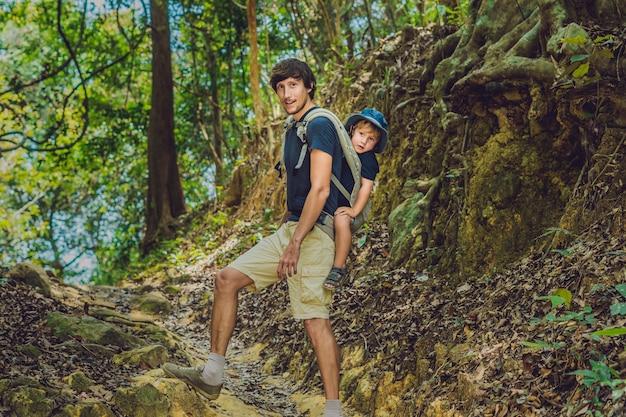 Il padre porta suo figlio in un bambino che trasporta sta facendo un'escursione nella foresta.