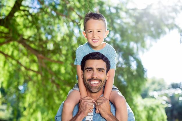 Padre che trasporta il figlio sulle spalle