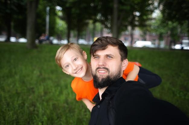 Il padre e il bambino fanno un selfie guardando la telecamera e ridono allegramente il bambino è in piedi dietro