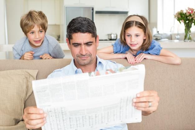 Padre e figli leggendo il giornale