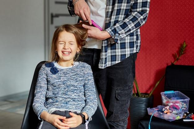 Padre che pettina, spazzola i capelli di sua figlia a casa, bambino che fa smorfie sul tirarsi i capelli