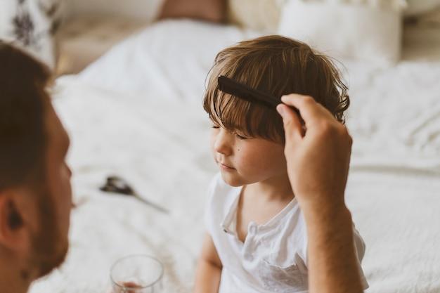Il padre taglia i capelli di suo figlio nella stanza. famiglia durante la quarantena