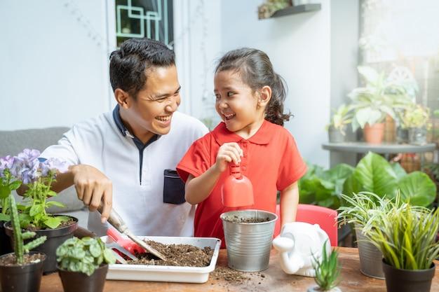 Padre e figlia sono felici quando usano una pala per coltivare piante in vaso