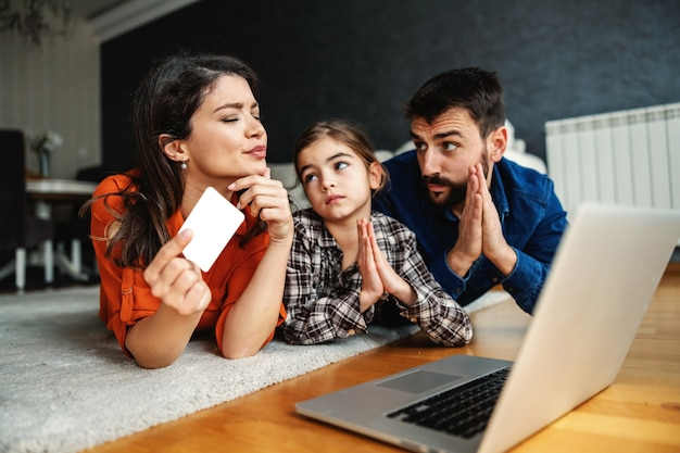 Padre e figlia che implorano la madre di acquistare alcuni oggetti su internet.
