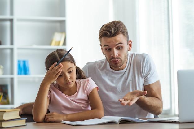 Il padre e una figlia che fanno i compiti alla scrivania