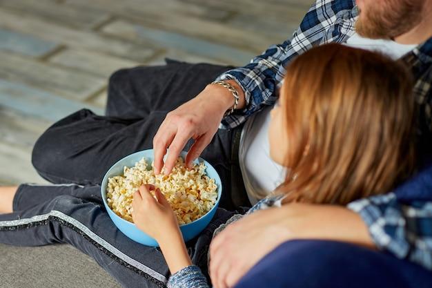 Padre e figlia mangiano popcorn e guardano film in tv