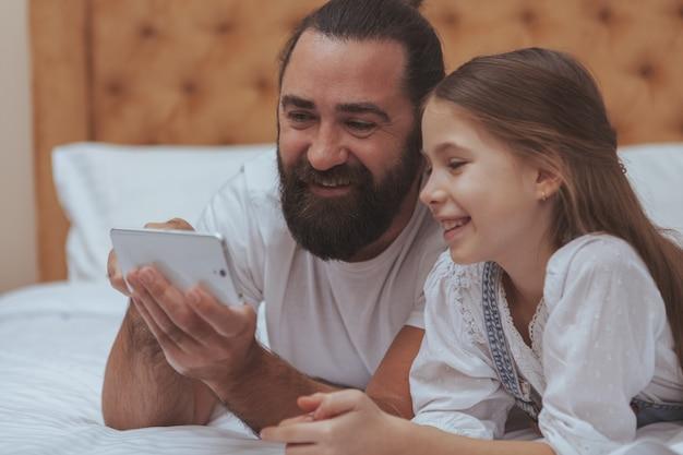 Padre e figlia che godono della giornata accogliente a casa