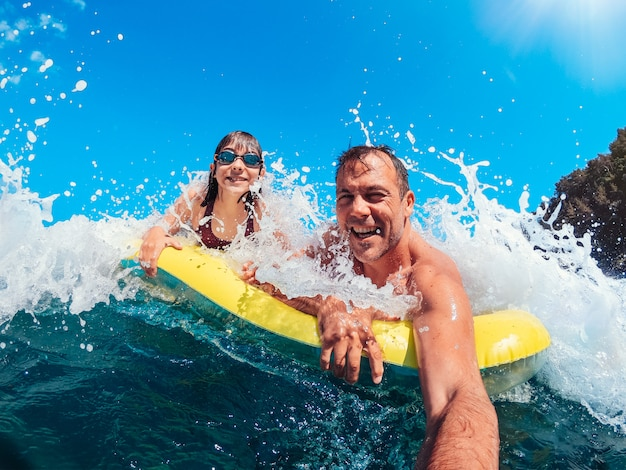 Padre e figlia divertirsi sulla spiaggia mentre si galleggia sul materassino