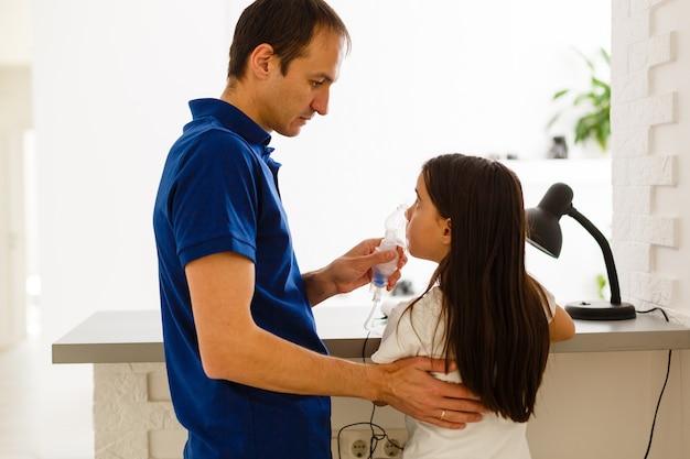 Padre e figlia fanno inalazioni. il papà premuroso aiuta sua figlia a respirare attraverso la maschera. trattamento delle vie respiratorie.