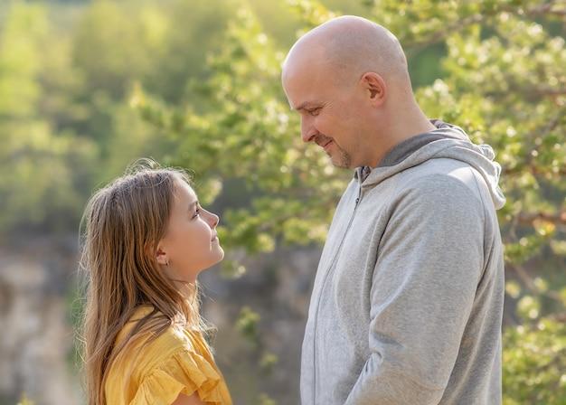 Padre e figlia si guardano e sorridono alla natura
