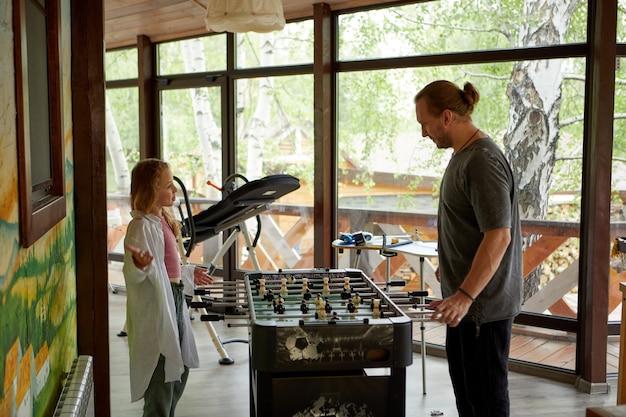 Padre e figlia giocano a biliardino nella pensione
