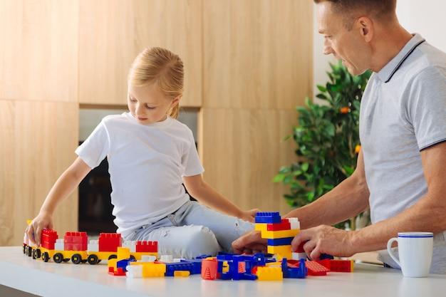 Padre e figlia che giocano con i giocattoli al chiuso