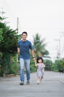 Padre e figlia che corrono per strada, concetto di famiglia