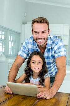 Padre e figlia che per mezzo della compressa digitale a casa