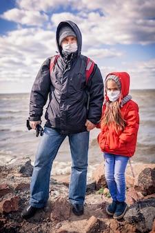 Padre e figlia che indossano maschere respiratorie che stanno insieme sulla riva del mare vuota all'inizio della primavera, stile di vita all'aperto, linee guida in tempo di quarantena