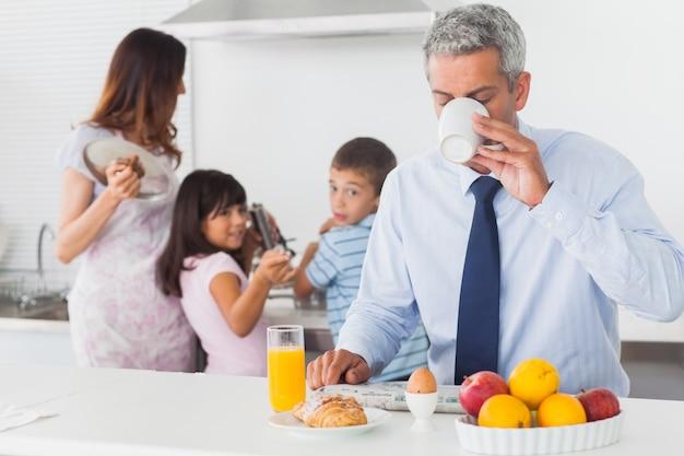 Papà mentre beve il caffè mentre la sua famiglia cucina in cucina
